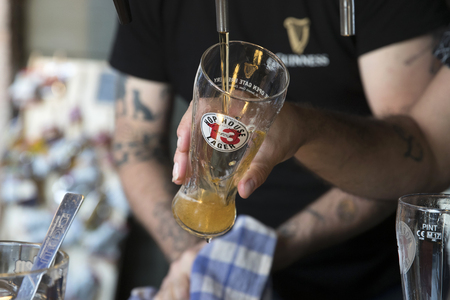 PIACENZA, ITALY - JUNE 15, 2018: horizontal closeup of a barman tapping a  Guinness Hop House 13 Lager in a bar