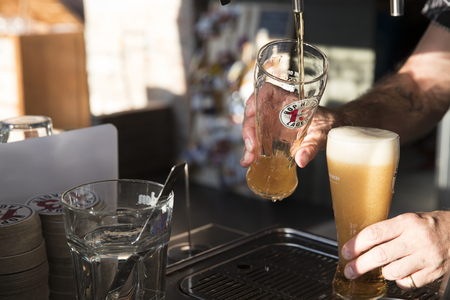 PIACENZA, ITALY - JUNE 15, 2018: Tapping a  Guinness Hop House 13 Lager behind a bar counter Editorial
