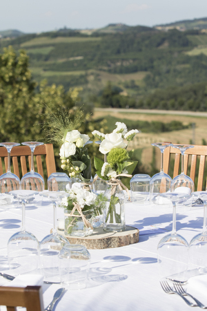 vertical shot of a wedding table setting with flowers  vases and seating for guests. Behind the table a beautiful view on the italian hills in Alba, Piemonte at sunset.