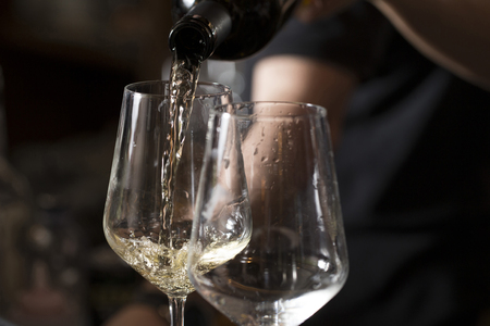 closeup of a barmaid is serving two glasses of prosecco on the bar cunter