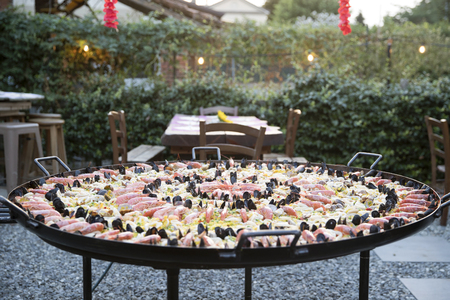 outdoor horizontal shot at sunset, a giant paellera with spanish fish paella in  a garden