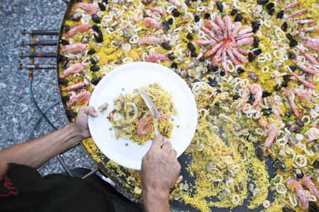 outdoor top view shot of a man serving paella