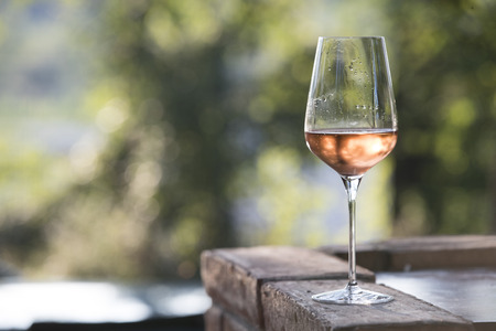 outdoor horizontal shot at sunset, an elegant glass of wine rosè. subject and focus on the right