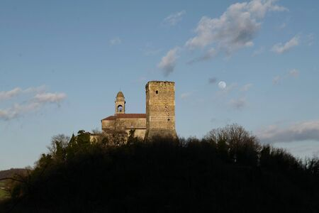 horizontal shot of Bobbiano Tower and church (in Travo, Piacenza) in Val Trebbia north Italy at sunset, with full moon rising on a sunny day with few cloud in the blue sky Banco de Imagens