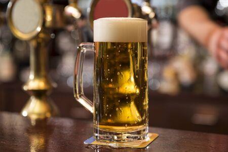 Primo piano orizzontale di una pinta di birra bionda in piedi sul bancone del bar davanti al rubinetto della birra
