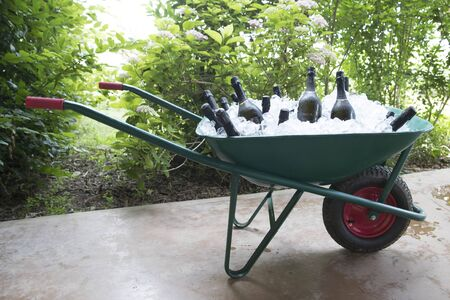 outdoor horizontal shot of a wheelbarrow full of ice and bottles of wine