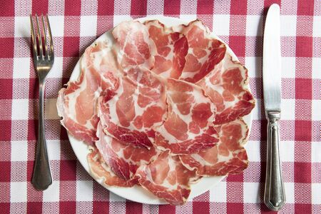 top view of a plate of coppa piacentina ( seasoned coppa made in Piacenza north italy) on a red and white table cloth Banco de Imagens