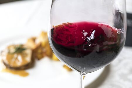 closeup of a glass of red italian wine moving into the glass with a meat dish on the back ground