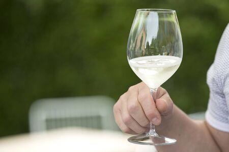outdoor closeup of a man holding a glass of prosecco Banco de Imagens