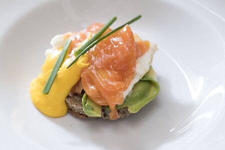 closeup of a plate of egg benedict with salmon, avocado and dutch sauce decorated with chives, subject and focus on the left Banco de Imagens