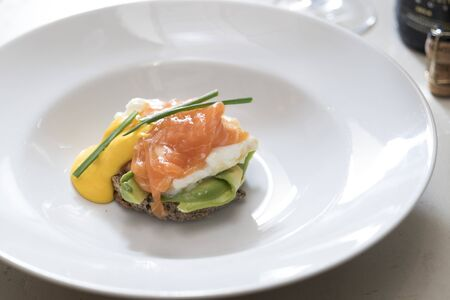 horizontal shot of a plate of egg benedict with salmon and dutch sauce decorated with chives, subject and focus on the left Banco de Imagens