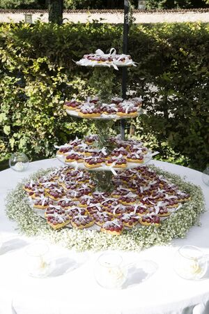 vertical shot of a wedding cake with hearth shaped cupcakes,  cream and fresh raspberries and flowers