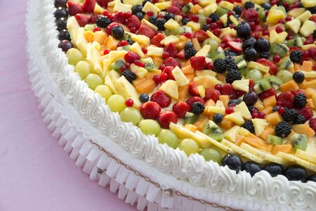 horizontal closeup of a wedding cake with whipped cream and fresh fruit on top
