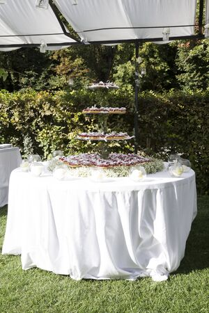 outdoor vertical shot of a round table with a wedding cake on top, the cake is made with hearth shaped cupcakes,  cream and fresh raspberries and flowers