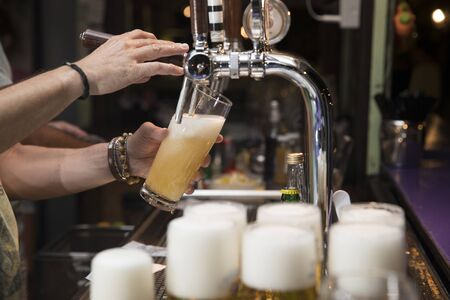 horizontal closeup of a bartender pouring a blonde beer in tap with subject and focus on the left