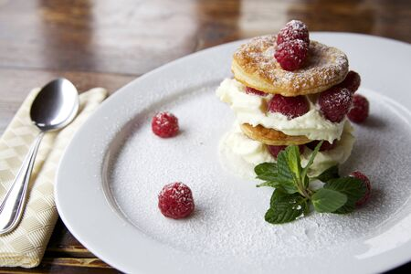 horizontal shot of a creamy and fresh dessert made with raspberry, puff pastry layers and fluffy cream. the plate is on a dark wooden table with a spoon on the left