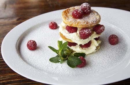 horizontal shot of a creamy and fresh dessert made with raspberry, puff pastry layers and fluffy cream. the plate is on a dark wooden table