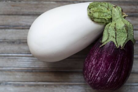 top shot closeup of one white aubergine next to a violet one on a wooden chopboard Banco de Imagens