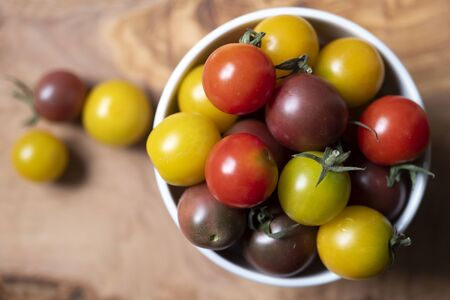 top view shot of a cup full of round and colored little tomatoes on a wooden chopboard.