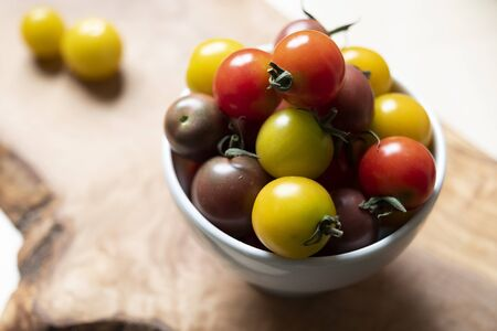 horizontal shot of a cup full of round and colored little tomatoes on a wooden chopboard. Banco de Imagens