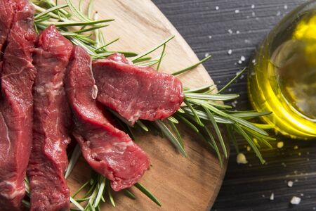 top view closeup of a raw italian tagliatelle, beef steak on a wooden chipboard with rosemary, salt and olive oil