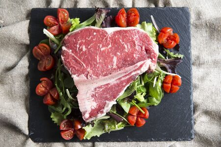 horizontal top view shot of a black slate plate with a raw t-bone steak italian fiorentina on it with cherry tomatoes