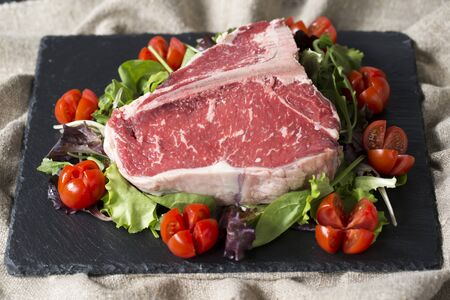 horizontal shot of a black plate made of slate with a raw t-bone steak on it and tomatoes with fresh salad. Stock fotó