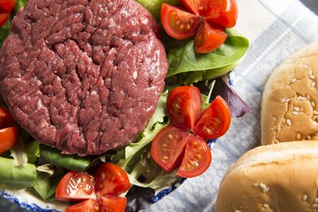top view closeup of a plate with a raw hamburger on it on a lettuce and tomatoes salad with hamburger breads. Banco de Imagens