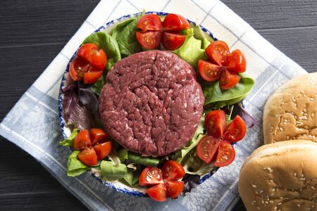 top view shot of a plate with a raw hamburger on it on a lettuce and tomatoes salad with hamburger breads. Banco de Imagens