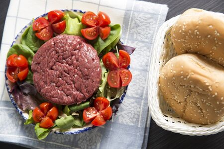 top view shot of a plate with a raw hamburger on it on a lettuce and tomatoes salad with hamburger breads on the right.