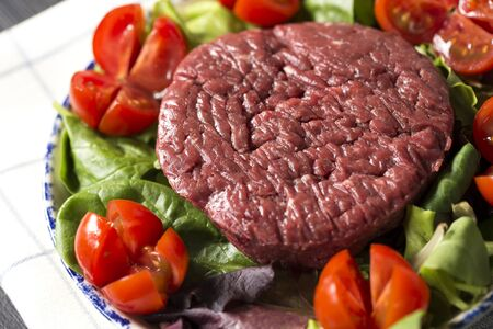 horizontal closeup of a plate with a raw hamburger on it on a lettuce and tomatoes salad.