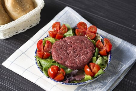 horizontal shot of a plate with a raw hamburger on it on a lettuce and tomatoes salad.