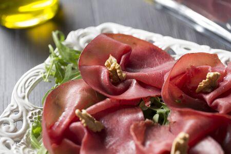 horizontal shot of italian thin sliced bresaola with walnuts on rocket salad. Bresaola is Seasoned raw meat from north italy.
