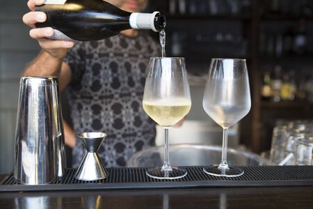 closeup of a barman serving prosecco in two cold wine glasses on the bar counter.