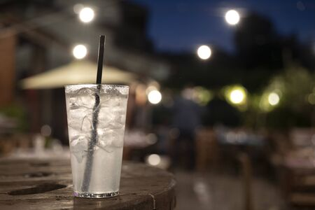 horizontal closeup of a gin tonic cocktail on a wooden table, outdoor night shot. subject and focus on the left. Banco de Imagens