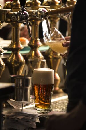 vertical closeup of a bartender pouring a dark beer in tap with subject and focus on the right