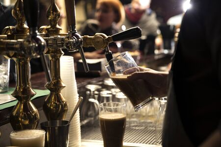 closeup of a bartender pouring a dark beer in tap behind the bar counter