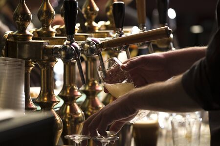 closeup of a bartender pouring a blonde double malt beer in tap behind the bar counter