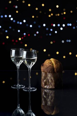 vertical night closeup of two elegant chrystal glasses with an italian panettone on black background with lights Stock Photo