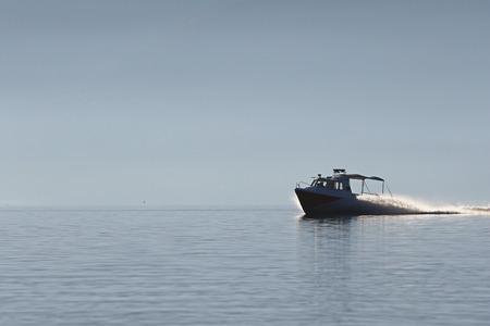 coast guard: Coast guard boat speeding in the mist