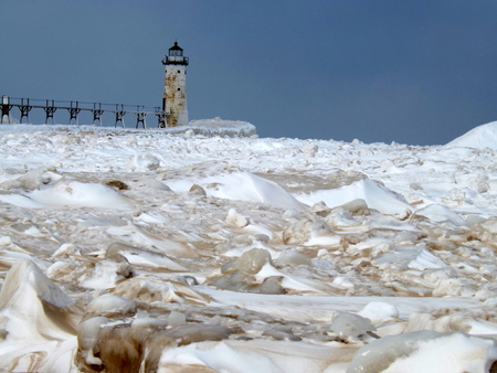 encapsulated: The lighthouse becomes virtually encapsulated by the frozen landscape  Stock Photo