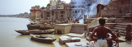 Man looks over the Manikarnika Ghat, main burning ghat, most auspicious place for Hindu to be cremated on banks of Ganges river, Uttar Pradesh, India