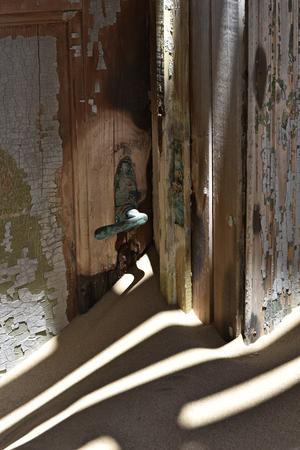 kolmanskop: by inside ancient building, the German abandoned ghost diamond town of Luderitz in Namibia Kolmanskop nearby