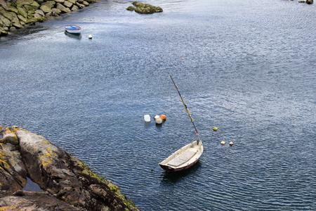 Two small white wooden boats anchored in a port next to a rock pier and cliffs with some buoys. Stock Photo