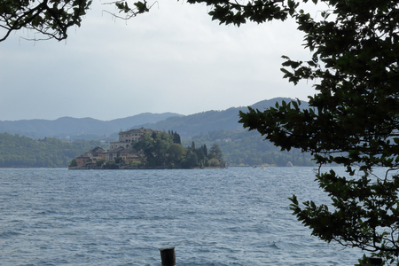 A landscape of Orta San Giulio island in the Orta Lake, in the Novara province in northern Italy, with branches and leaves of a tree