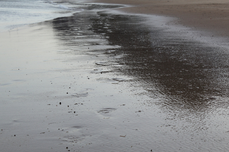 Wet Sahara sand in Las Teresitas beach in Tenerife with a wave and some human footsteps Foto de archivo - 107710092