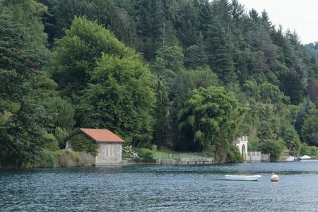 Una casa con alberi vicino alla riva del lago d'Orta in provincia di Novara, nel nord Italia, con una barca