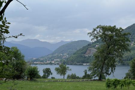 Un paesaggio del Lago d'Orta, nel nord Italia, con alberi e montagne a prua Archivio Fotografico