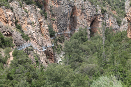 The Vero river canyon during a summer day with the hanging elevated path over it, the typical red iron rock and some trees, in Alquezar, Spain Banco de Imagens