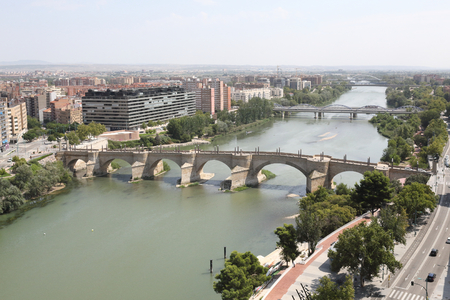 A landscape of Zaragoza city, with Ebro river shores, the Stone and Iron bridges, a seen from the Pilar Catedral bell tower, Spain